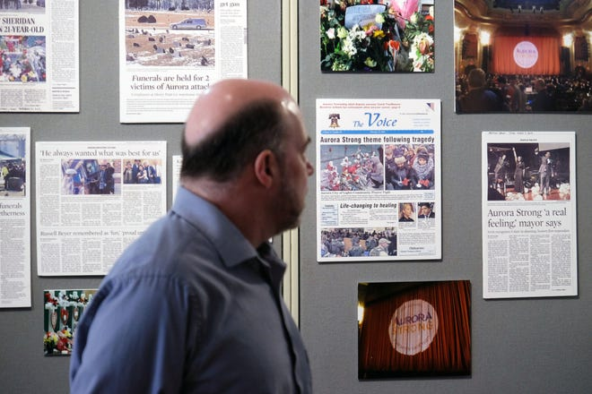 John Jaros, executive director of the Aurora Historical Society, stands before a display at the David L. Pierce Art & History Center in Aurora, Ill. on Feb. 14, 2020. The historical society remembered the one-year anniversary of a mass shooting by putting up an exhibit to honor the victims.