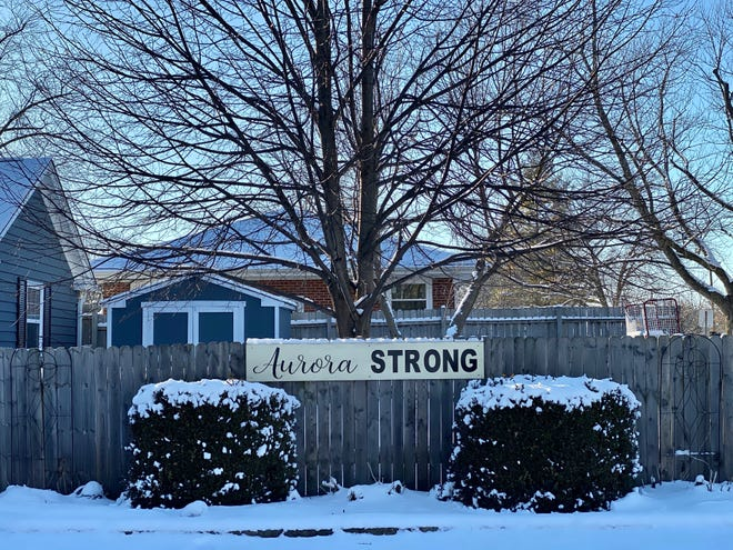 """A resident displays an """"Aurora Strong"""" sign on their fence along Western St. in Aurora."""