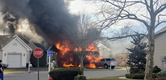 A fire burns a home on Sunday near the intersection of Butler Avenue and Cranmer Road in the Bayville section of Berkeley.