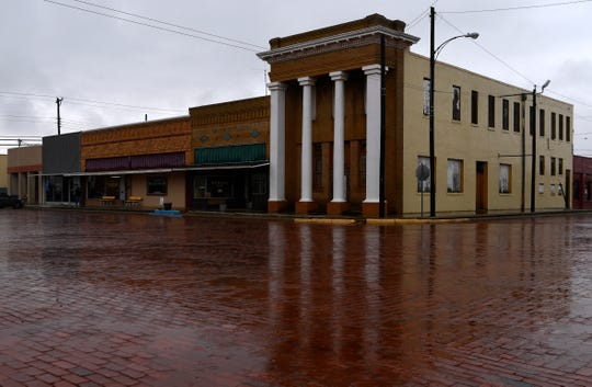 """Rainwater reflects the columns on a building at the corner of North Second and Edwards streets in Merkel. A local group has submitted an application for the new HGTV show """"Home Town Takeover,"""" in which a town is renovated over a season."""