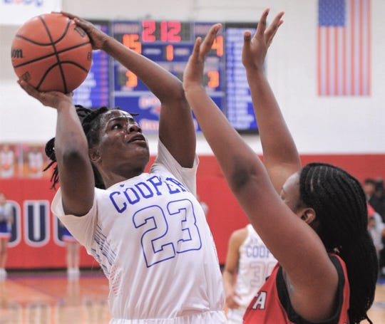 Cooper's Dazz Larkins (23) shoots over a Wichita Falls High defender. Cooper beat the Lady Coyotes 71-29 in the District 4-5A game Jan. 11 at Cougar Gym.
