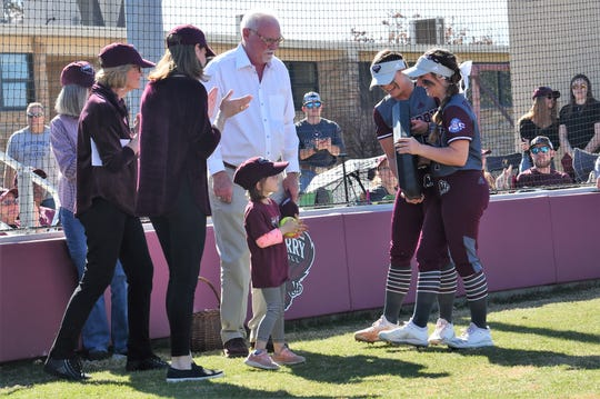 McMurry softball players Hope Schoeneman (5) and Sarah Nagy (1) present a commemorative home plate to the Edwards family during the dedication of Edwards Field on Sunday, Feb. 16, 2020. The War Hawks opened the field with a doubleheader against Southwestern following the ceremony.
