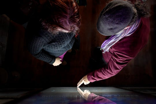 Paul Gallimore, right, of Charlotte, touches an interactive screen as Tina White looks on at the new LEAF Global Arts Center in downtown Asheville on Feb. 14, 2020. Gallimore volunteered his time to help create mapping for the interactive kiosks.