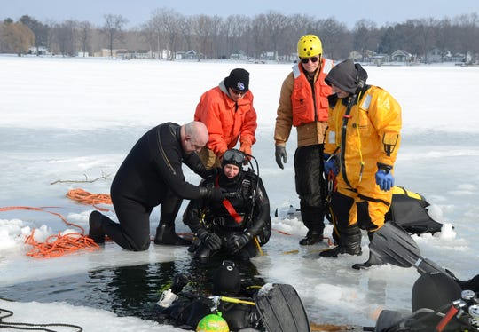 Dave Winder is pulled from the water after his first ice dive on Sunday during a training exercise on Lee Lake in Calhoun County's Newton Township.