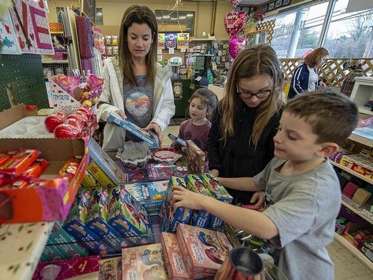 Jill Gounaris, of Medford, and her children, Hailey, Brooke and Dane, shop at Binkley's on Stokes Road.