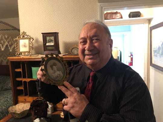 John Leone, a trustee of the Gloucester County Historical  Society in Woodbury, holds a portrait of his great-aunt Sybil Tatum Jones, who was a founder and live-in curator of the GCHS museum.