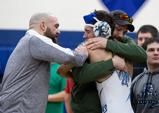 Adena junior Garrett Simmons is congratulated by his head coach Dalton Moss, left, while emotionally hugging his father Cecil Simmons after defeating Westfall junior Marcus Whaley by a 11-8 decision in a 132-pund match during the 2019-2020 Scioto Valley Conference (SVC) wrestling championships held at Southeastern High School on Feb. 15, 2020. Garrett would take first place in his weight class.