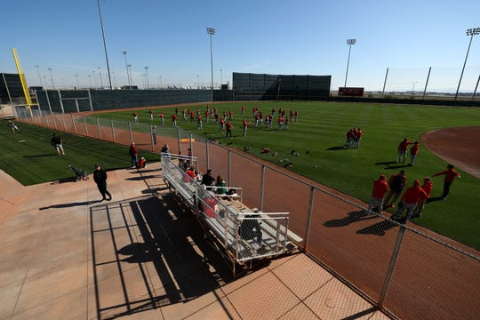 Cincinnati Reds fans watch as pitchers begin stretching, Sunday, Feb. 16, 2020, at the Cincinnati Reds Spring Training Facility in Goodyear, Arizona.