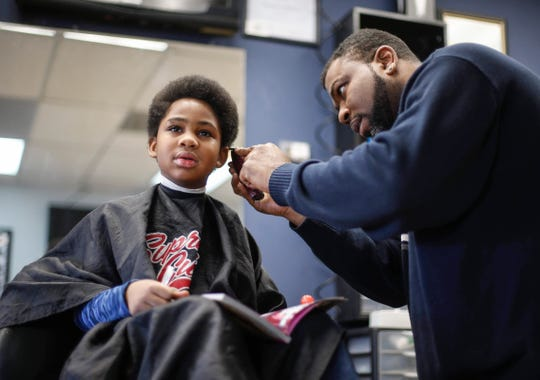 Barber Lance Williams Sr, cuts the hair of Amaru Johnson, 7, of Des Moines, as Johnson reads a book during Storybook Sundays at Supreme Cuts in Des Moines on Sunday, Feb. 16, 2020. Williams began Storybook Sundays as a way to help the Des Moines community improve literacy.