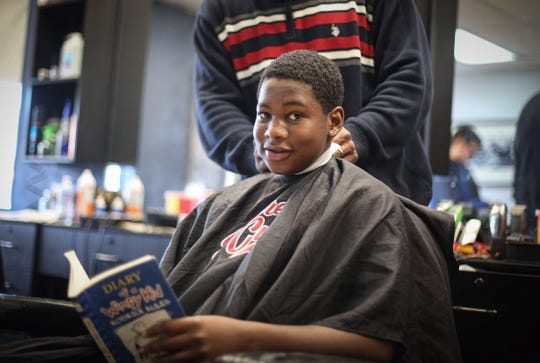Barber Lance Williams Sr, cuts the hair of Djalin Marshall, 15, of Des Moines, as Marshall reads a book during Storybook Sundays at Supreme Cuts in Des Moines on Sunday, Feb. 16, 2020. Williams began Storybook Sundays as a way to help the Des Moines community improve literacy.