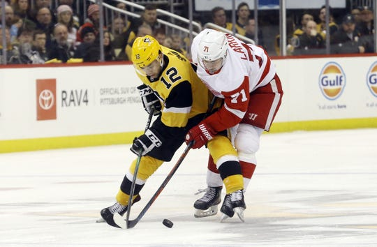 Pittsburgh Penguins center Dominik Simon and Detroit Red Wings center Dylan Larkin battle for control of the puck during the third period at PPG PAINTS Arena in Pittsburgh, Feb. 16, 2020.