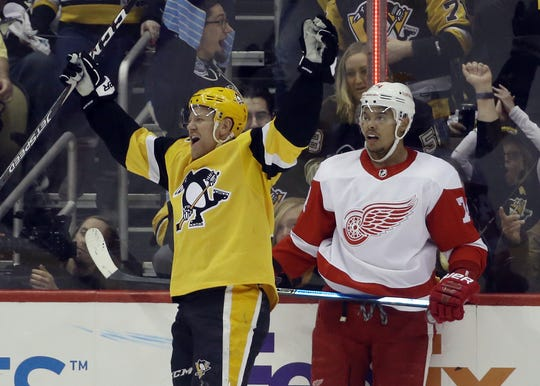 Pittsburgh Penguins right wing Patric Hornqvist reacts to scoring his third goal to record a hat-trick against the Detroit Red Wings during the second period at PPG PAINTS Arena in Pittsburgh, Feb. 16, 2020. Wings defenseman Madison Bowey at right.