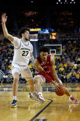 Indiana's Justin Smith dribbles while defended by Michigan's Brandon Johns Jr. in the second half Sunday, Feb. 16, 2020, in Ann Arbor.