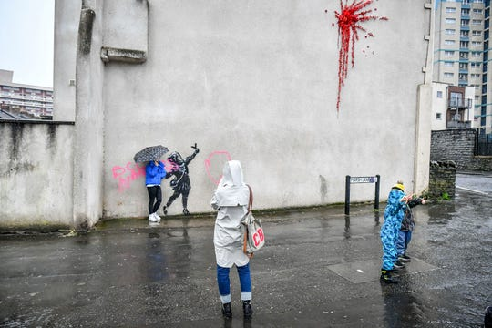 People take photos of a mural by Bansky which has been vandalised, on the side of a house on Marsh Lane, in Barton Hill, Bristol, England, Saturday, Feb. 15, 2020.