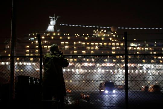 A photographer takes pictures of the quarantined Diamond Princess cruise ship docked at Yokohama Port, near Tokyo, Sunday, Feb. 16, 2020.