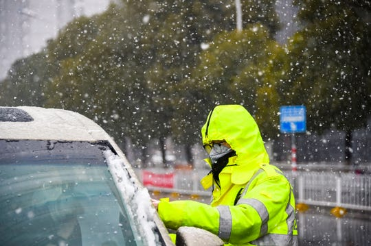 In this photo released by China's Xinhua News Agency, a traffic policeman wearing a face mask checks a car during a snowfall in Xiaogan in central China's Hubei Province, Saturday, Feb. 15, 2020.