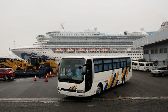 A bus leaves the quarantined Diamond Princess cruise ship at a port Sunday, Feb. 16, 2020, in Yokohama, near Tokyo.