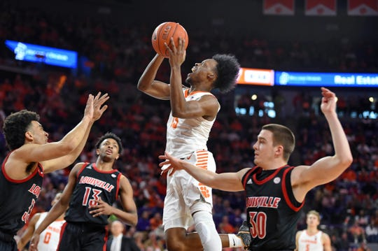 Clemson's John Newman lll (15) drives to the basket as Louisville's Jordan Nwora, left, David Johnson, center, and Ryan McMahon defend during the first half Saturday.