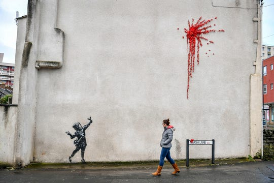 A woman walks past a new artwork on the side of a house in Bristol, England, Thursday Feb. 13, 2020, which has been confirmed as the work of street artist Banksy.
