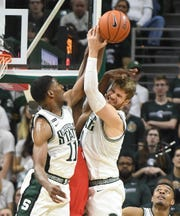 Spartans' Aaron Henry and Kyle Ahrens collide with Maryland's Jalden Smith bringing down a rebound in the second half.