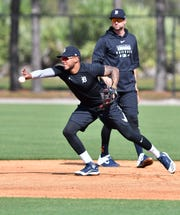 Tigers second baseman Jordy Mercer, rear, watches while Harold Castro tosses the ball to second base during a voluntary workout. They both look like good bets to make the Tigers roster.