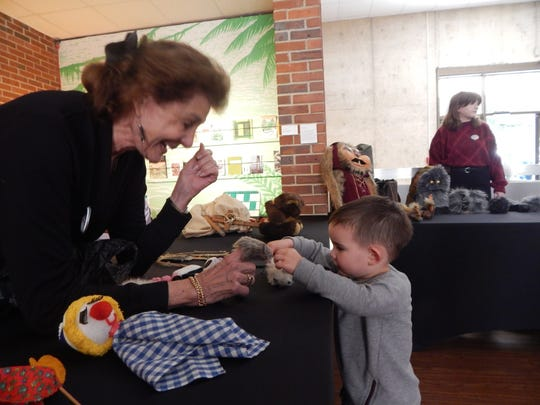 Jan Kaufman demonstrates to a curious boy the workings of the finger puppet.