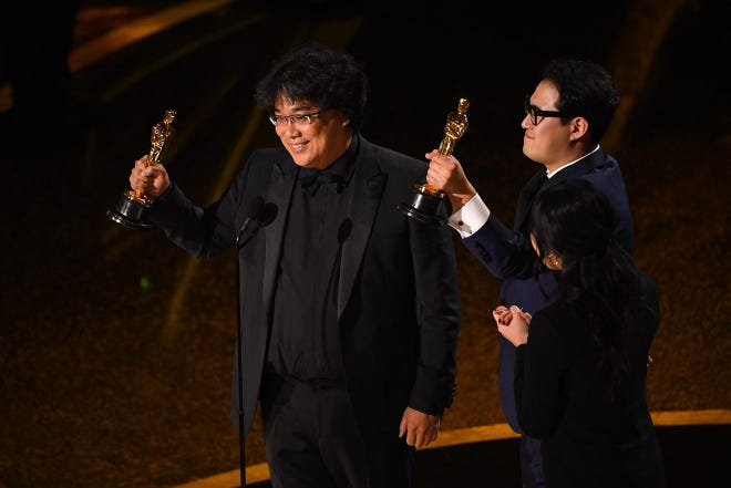 "Bong Joon-Ho (left) and Han Jin Won accept the award for best original screenplay for ""Parasite"" during the 92nd Academy Awards at Dolby Theatre."