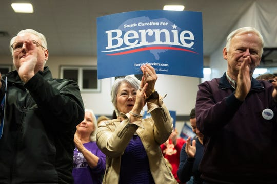 Robert Herrick (from left), of Inman, and Ann and Terry Bailey, of Greenville, applaud speakers at the end of an event held by Bernie Sanders' campaign at the West End Community Development Center Saturday, Feb. 15, 2020.
