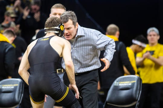 Tom Brands, right, congratulates Austin DeSanto after a 24-8 technical fall in his return to the Iowa lineup against Minnesota.