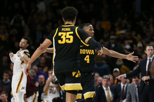 Iowa's Bakari Evelyn (4) and Cordell Pemsl celebrate a 58-55 win over Minnesota on Sunday at Williams Arena. Evelyn made the two free throws that gave the Hawkeyes the lead for good with 1:15 remaining.