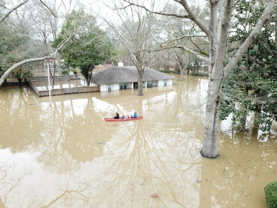Nate Green (far right), his two children and Clarion Ledger reporter Wilton Jackson canoe through Jackson streets during severe flooding on Sunday, Feb. 16, 2020.