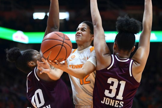 Tennessee's Rae Burrell (12) gets caught between Texas A&M center Ciera Johnson (40) and forward N'Dea Jones (31) in Sunday's game.