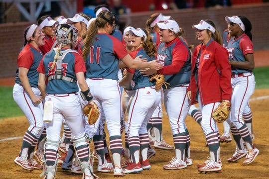 Play is suspended for the nationally ranked UL softball team, shown here congratulating Kaitlyn Alderink after an impressive catch during a win over LSU earlier this seasn, due to coronavirus.