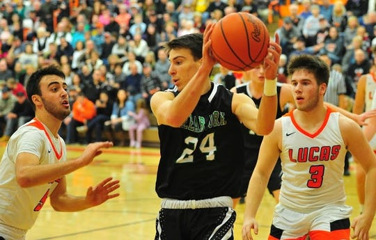 Clear Fork's Brennan South finds himself surrounded by Lucas' Ethan Sauder (5) and Ethan Wallace (3) Saturday night in a packed Lucas gymnasium.