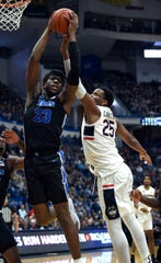 Memphis center Malcolm Dandridge (23) grabs a rebound over UConn center Josh Carlton (25) in Sunday's game.