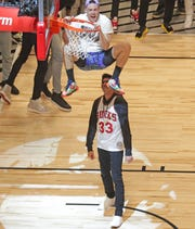 "Pat Connaughton of the Bucks hangs on the rim after dunking over Brewers outfielder Christian Yelich in the first round of the dunk contest Saturday night in Chicago. Connaughton dressed as Woody Harrelson's character, Billy Hoyle, from the 1992 movie ""White Men Can't Jump"" for his first attempt. Yelich was wearing a vintage Kareem Abdul-Jabbar Bucks jersey."