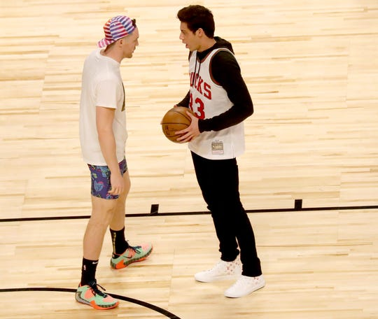 Pat Connaughton of the Bucks goes over his dunk plan with Brewers outfielder Christian Yelich during the first round of the dunk contest.
