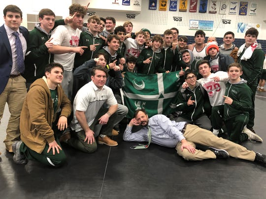 Led by head coach Bryan Stoll (front), Delbarton defeated St. Augustine for its first NJSIAA Non-Public A wrestling championship since 2011.