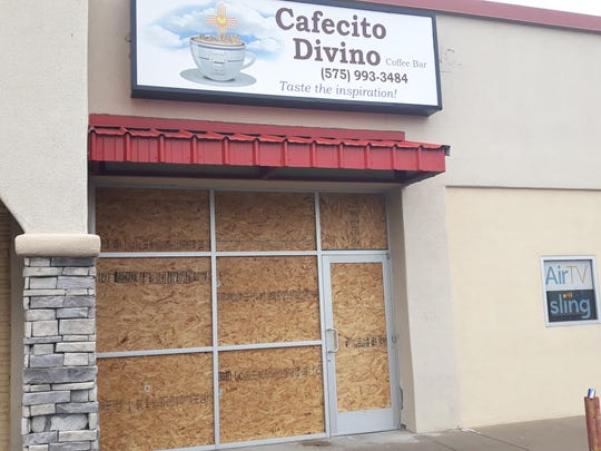 The storefront of Cafecito Divino is boarded up after a pickup truck drove through the front of the shop on Jan. 12, 2020.