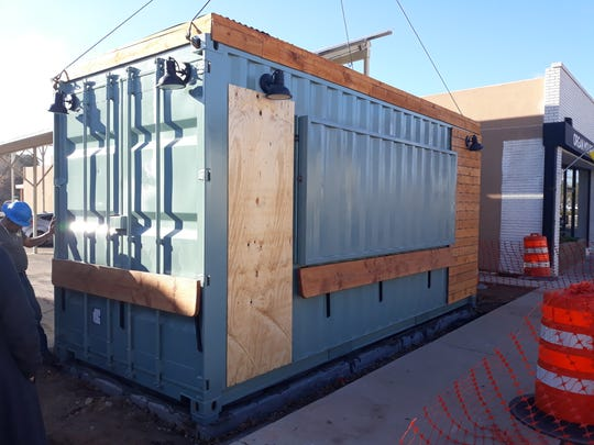 A shipping container, the future location of Beck's Express, is lowered into place next to Organ Mountain Outfitters on South Main Street in Las Cruces on Wednesday, Feb. 12, 2020.