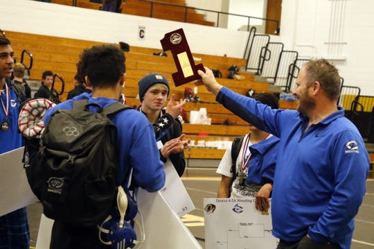 Carlsbad athletic director James Johns presents the Cavemen with the first place District 4-5A Championship plaque in Hobbs on Feb. 15, 2020. Carlsbad won the tournament and will be sending 12 boys and 5 girls to the state tournament in Rio Rancho on Feb. 21.