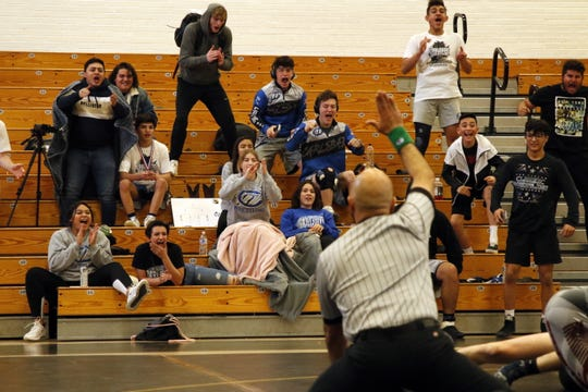The Carlsbad wrestling team reacts to Logan Romero taking down Roswell's Jaymon Cherinko in the championship round of the 120-pound division at the District 4-5A Championship in Hobbs on Feb. 15, 2020. Romero won with a pinfall in 44 seconds and advances to the state tournament with the win.
