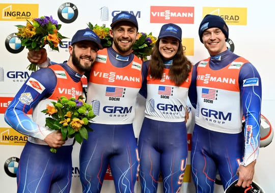 United States's team Jayson Terdiman, left, Chris Mazdzer, second left, Summer Britcher, second right, and Tucker West placed third, celebrate after the World Cup luge relay event in Krasnaya Polyana, near the Black Sea resort of Sochi, southern Russia, Sunday, Feb. 16, 2020. (AP Photo/Artur Lebedev)