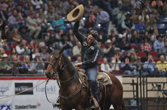 Ty Harris salutes the hometown crowd after competing in the tie down roping event at the Cinch Chute-Out at the San Angelo Stock Show and Rodeo on Saturday, Feb. 15, 2020.