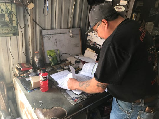Mertzon resident Ray Montez consults his notes regarding the newly expanded effluent pit located several feet behind his home and business during an interview on Saturday, Feb. 16, 2020.