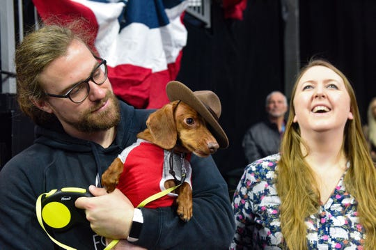Beanz, dressed as a Canadian mounty, is held by owners Michael Young and Kimberly DesBrisay following the 13th annual Weiner Dog Race on Saturday, Feb. 15, at the Denny Sanford Premier Center in Sioux Falls.