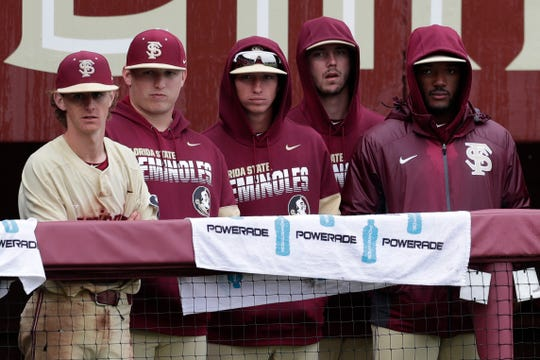 Players in the dugout try to stay dry as they watch their team during a rainy game between FSU and Niagara University Dick Howser Stadium Sunday, Feb. 16, 2020.
