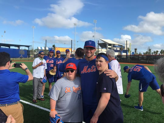 New York Mets outfielder Tim Tebow takes a picture with Special Olympians Grant Newell (left)  and Connor Marks on Sunday at the Spring Clinic for Champions at Clover Park on Sunday.