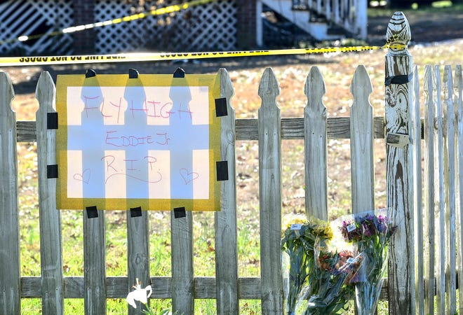"""Flowers are are set near a sign """"Fly High Eddie Jr. R.I.P."""", where Charles Edward Tate, Jr., 29 and Christine Ann Bagwell, 21, died inside a home on Whitten Road home in Pelzer Saturday, according to a release from the Anderson County Coroner's Office."""