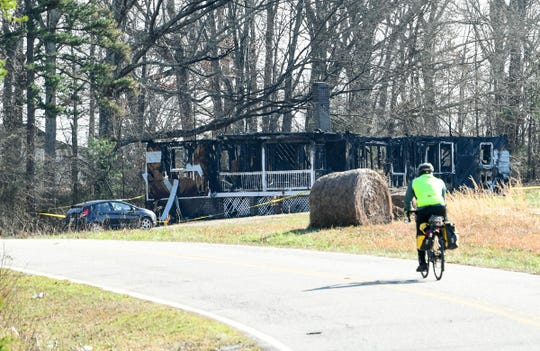 A bicyclist rides by where Charles Edward Tate, Jr., 29 and Christine Ann Bagwell, 21, died inside a home on Whitten Road home in Pelzer Saturday, according to a release from the Anderson County Coroner's Office.